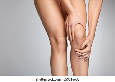 Pain In Knee. Closeup Of Beautiful Female Leg With Painful Knees. Close-up Of Woman Feeling Joint Pain, Having Health Issues And Touching Leg With Hands. Body And Health Care Concept. High Resolution