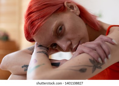 Pain and misery. Close up of red-haired woman with tattoos feeling pain and misery suffering from anorexia