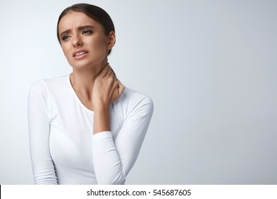 Pain In Neck. Portrait Of Beautiful Young Woman Suffering From Body Pain. Attractive Female Feeling Tired, Exhausted, Stressed, Holding Hand On Painful Shoulders. Health Care Concept. High Resolution