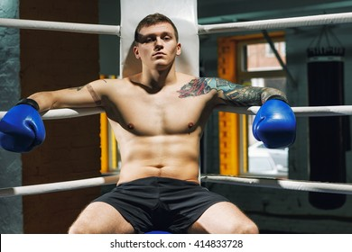 Pain is nothing. Confident young fighter sitting in a corner of a boxing ring.