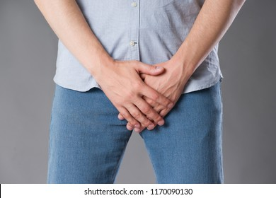 Pain in prostate, man suffering from prostatitis or from a venereal disease, studio shot on gray background