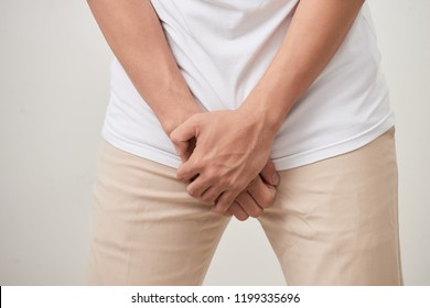 Pain in prostate, man suffering from prostatitis or from a venereal disease, studio shot on white background