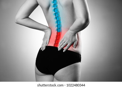 Pain in the spine, woman with backache, injury in the lower back, black and white photo with highlighted skeleton