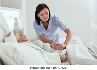 Pain in stomach. Active pleasant nurse touching stomach while elder woman lying in bed