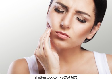 Pain. Teeth Problem. Woman Feeling Tooth Pain. Closeup Of A Beautiful Sad Girl Suffering From Strong Tooth Pain. Attractive Female Feeling Painful Toothache. Dental Health And Care Concept.
