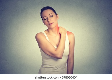 pain. Woman with painful neck shoulder colored in red isolated on gray wall background