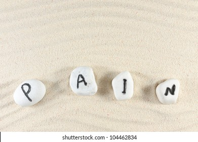 Pain word on group of stones with sand background