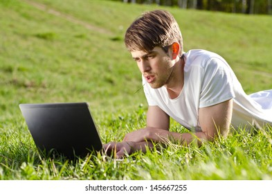 A pained student working on his laptop computer on the grass