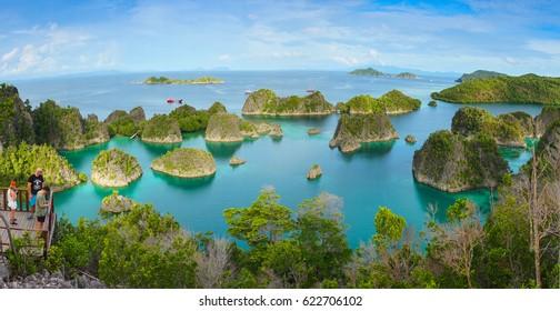 Painemo Island, Indonesia - April 04, 2017: Tourists, Caucasian people, at Blue Lagoon, in Raja Ampat marine park, West Papua, Indonesia, Asia. Horizontal panoramic view