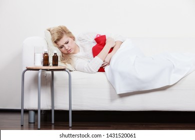 Painful periods and menstrual cramp problems concept. Woman having stomach cramps lying on cofa feeling very unwell holding hot water bottle to feel some relief
