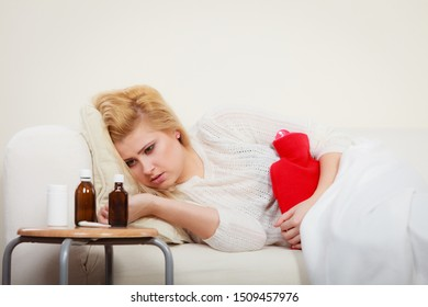 Painful periods and menstrual cramp problems concept. Woman feeling stomach cramps lying on cofa feeling very unwell looking at medicines.