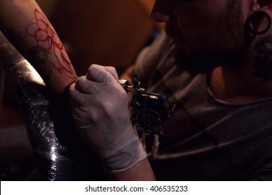 Painful procedure of getting tattoo from professional tattoo artist