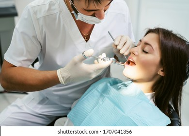 Painkiller anesthesia injection. Dentist examining a patient's teeth in modern dentistry office. Closeup cropped picture with copyspace. Doctor in disposable medical facial mask.