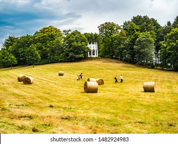 Painshill Park, Cobham Surrey, England. 4 August 2019. Painshill Park Surrey a family running across a yellow grass filed past hay bales with a white folly in the background.
