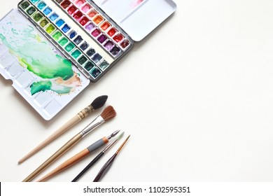 Paint accessories and watercolor And Blank Book on Wooden Table. (workplace mock up,Copy Space,Isolated, White Copy space,Color Copy space, Blank Copy Space, Wood Copy Space, Paint mock up.)