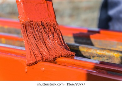 Paint application by brush on metal structures. Protective coating of steel closed profiles with primer iron oxide red.