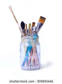 Paint art brushes in a glass jar isolated over white background.