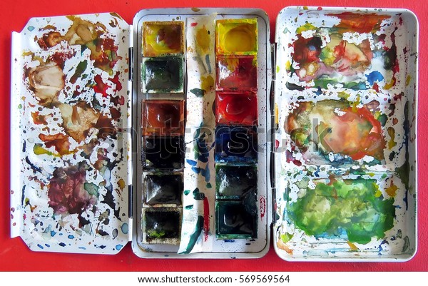 Paint box of watercolors on red table