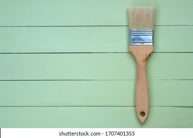 Paint brush with bristles and a wooden handle on a green background. Wooden pale green boards background top view. Wooden painted planks and a small brush with natural bristles.