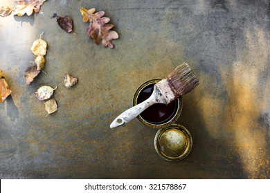 Paint brush, can of oil and autumn leaves on an old, rusty metal surface