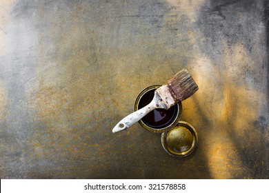 Paint brush, can of oil on an old, rusty metal surface