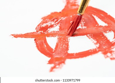 Paint brush drawing anarchy symbol on the paper.