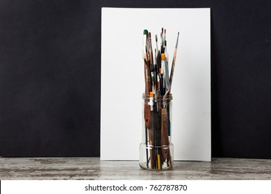 Paint brush in a glass, next white canvas. Ð?n a black background. With copy space.