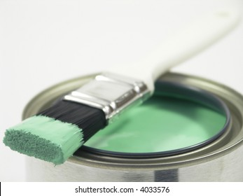 Paint brush lying across top of paint can. Shallow DOF focus on front of brush.