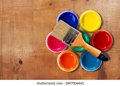 Paint brush on a jar with colored paint on a wooden background. Repairing concept.