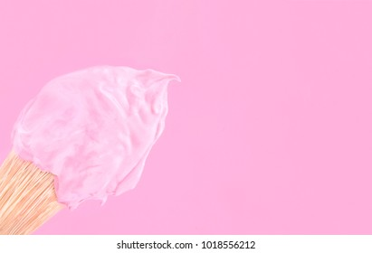 Paint brush on pink paper background.