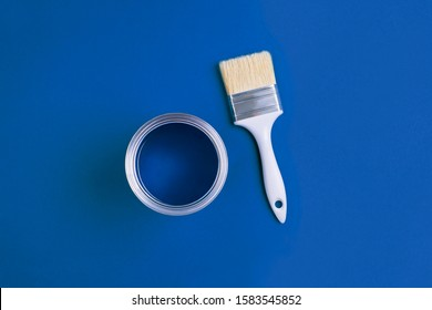 Paint brush with an open can of paint on trendy Classic Blue background. Color of the year 2020. Top view, flat lay.