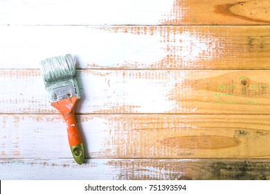 Paint brush and painted on wood wall with white color