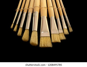 Paint Brush set layed out on black background, up close