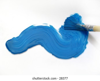 Paint brush smearing blue paint onto a white surface.