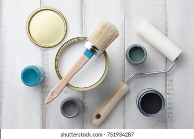 Paint brush, sponge roller, paints, waxes and other painting or decorating supplies on white wooden planks, top view - Shutterstock ID 751934287