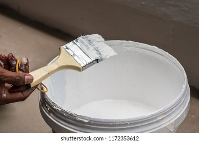 Paint brush and white color paint bucket