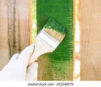 paint brush with wooden handle and dab of green paint , painting wooden furniture, close up, hand in protective glove cotton brush paints the wooden fence, a painter paints construction