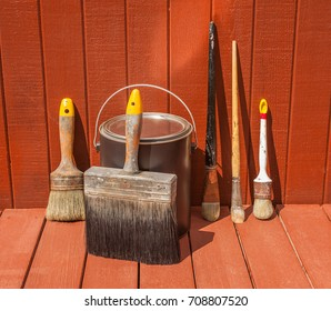 Paint brushes against a just painted wood house exterior
