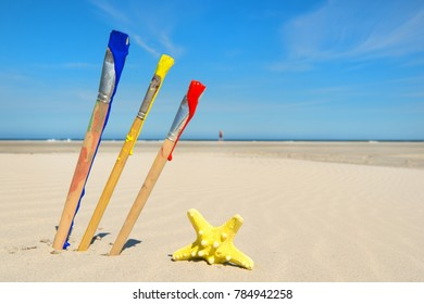 Paint brushes in blue yellow and red at te beach