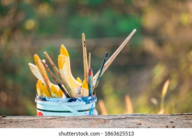 Paint brushes in the bucket on the ground.