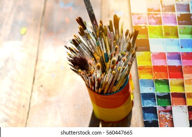 Paint brushes in the cup and palette water paints are on the table