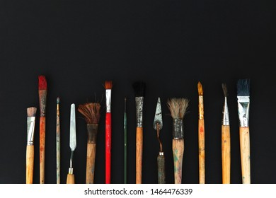 Paint brushes of different sizes and mastehin on the black background.