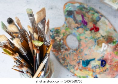 Paint brushes in a glass close-up on the background of a palette, paints and canvas.