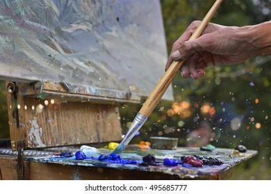 Paint brushes in the hands of the artist. girl artist.