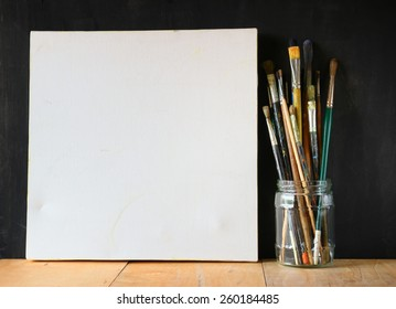paint brushes in jar and blank canvas over blackboard background