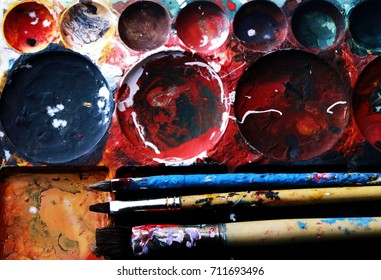 paint brushes l on a color ful painter in black ground. Tool for artistic in studio.