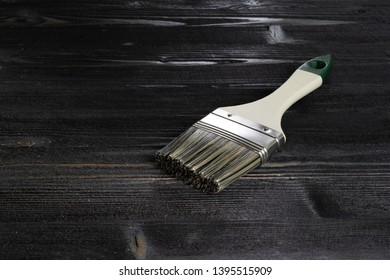 Paint brushes on dark ebony wood desk surface