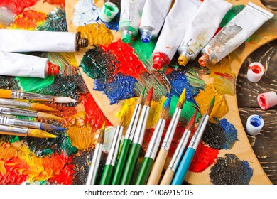 Paint brushes and paint on an old background in a composition on a table