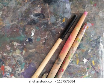 Paint brushes on old painting palette