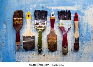Paint brushes on old wood blue surface